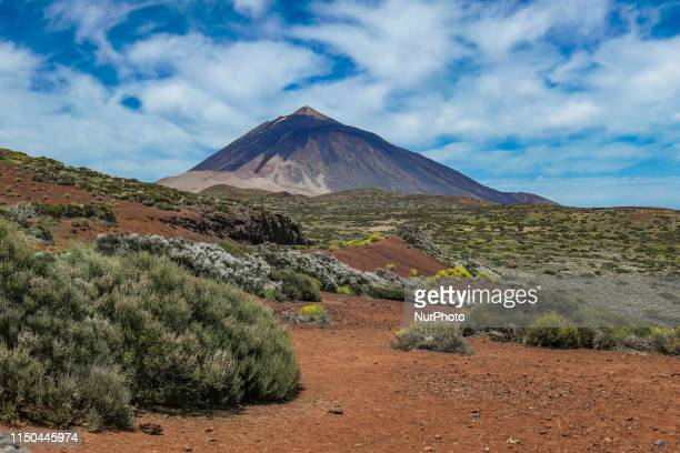 El Teide volcano mountain peak in Tenerife, Canary islands of Spain with blue sky and clouds as seen from the northeast side of the island, a...