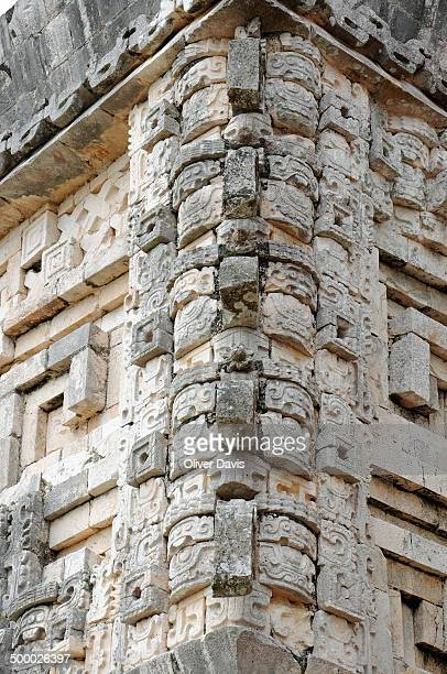 Elaborate facade of Governor's Palace building featuring a mosaic of geometric shapes, glyphs and sculptures. Uxmal UNESCO World Heritage Site.