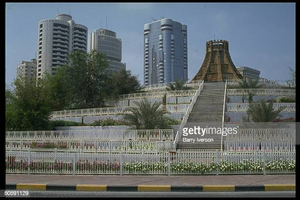 Elaborate stone fountain w castle turretlike shape gracing corniche area w office towers looming beyond