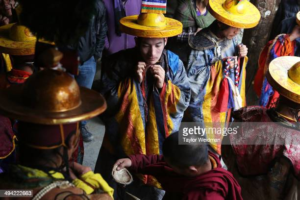 Elaborately dressed monks prepare to perform ceremonies in the main square during the Tenchi Festival on May 25 2014 in Lo Manthang Nepal The Tenchi...