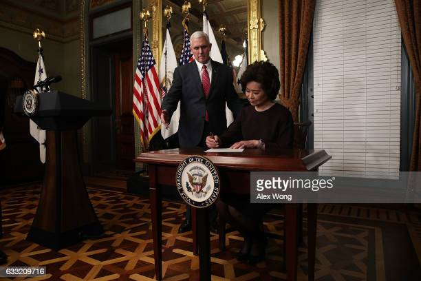 Elaine Chao signs the affidavit of appointment as US Vice President Mike Pence looks on during a swearing in ceremony at the Vice President's...