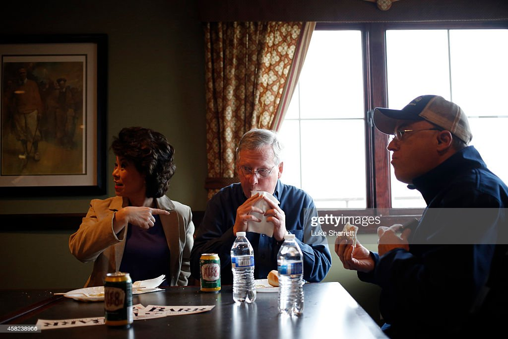 Elaine Chao sits next to her husband Senate Minority Leader Mitch McConnell (R-KY) as he eats a hot dog during a campaign rally and hot dog roast at the Old Silo Golf Course and Clubhouse on November 1, 2014 in Mt. Sterling, Kentucky. The most recent Bluegrass Poll shows McConnell with a five point lead over Democratic challenger Alison Lundergan Grimes.