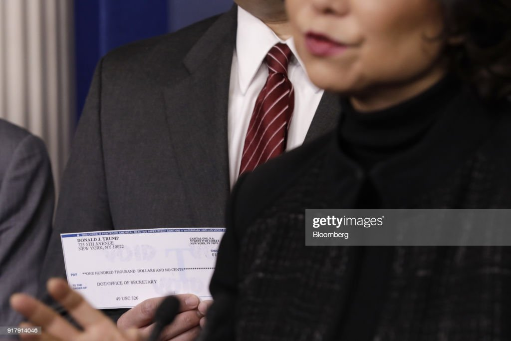 Elaine Chao, U.S. transportation secretary, right, speaks while Derek Kan, U.S. transportation undersecretary, holds a check from U.S. President Donald Trump, donated from his quarterly salary, to the Department of Transportation during a White House press briefing in Washington, D.C., U.S., on Tuesday, Feb. 13, 2018. Chao said the gas tax is an option but not 'ideal.' Photographer: Yuri Gripas/Bloomberg via Getty Images