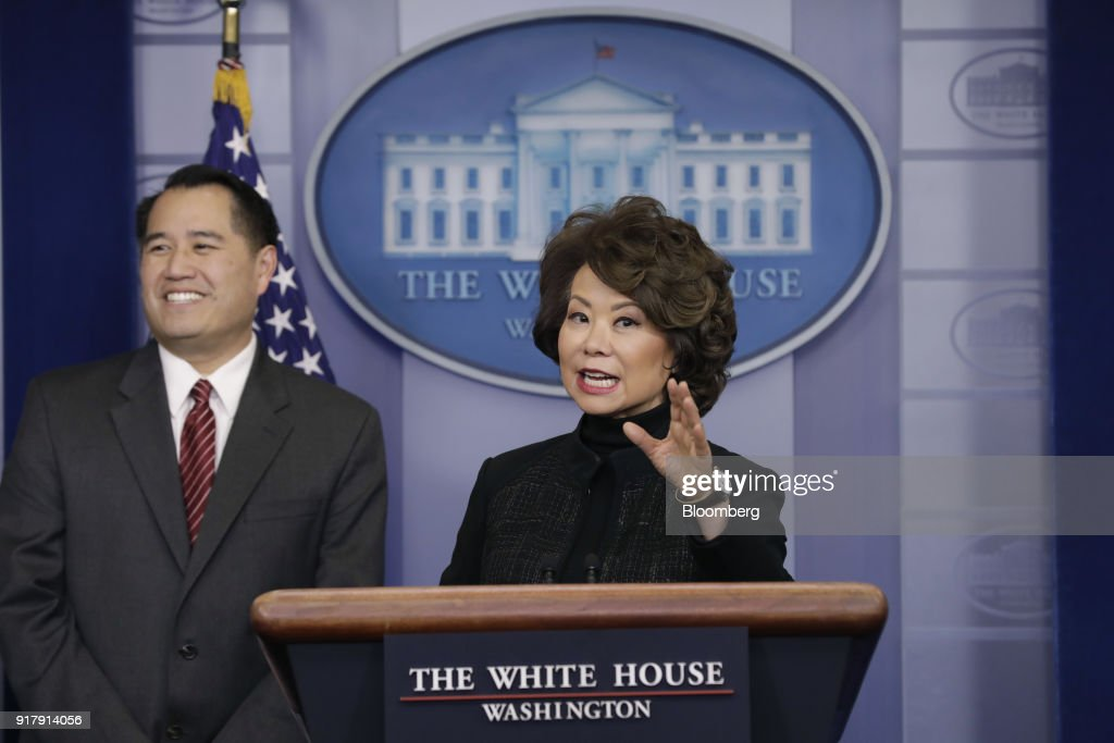 Elaine Chao, U.S. transportation secretary, right, speaks while Derek Kan, U.S. transportation undersecretary, listens during a White House press briefing in Washington, D.C., U.S., on Tuesday, Feb. 13, 2018. Chao said the gas tax is an option but not 'ideal.' Photographer: Yuri Gripas/Bloomberg via Getty Images