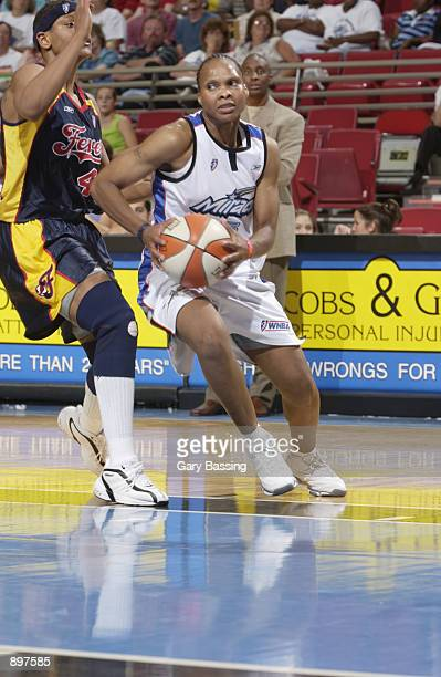 Elaine Powell of the Orlando Miracle drives around Alicia Thompson of the Indiana Fever in the game on June 11 2002 at TD Waterhouse Centre in...