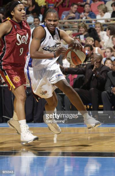 Elaine Powell of the Orlando Miracle drives past Claudia Neves of the Miami Sol in the game on June 15 2002 at TD Waterhouse Centre in Orlando...