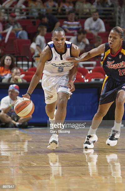 Elaine Powell of the Orlando Miracle drives upcourt defended by Nikki McCray of the Indiana Fever in the game on June 11 2002 at TD Waterhouse Centre...