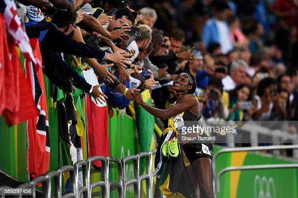 Elaine Thompson of Jamaica celebrates with the crowd after winning the Women's 100m Final on Day 8 of the Rio 2016 Olympic Games at the Olympic...