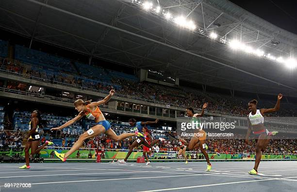 Elaine Thompson of Jamaica crosses the line to win gold in the Women's 200m Final ahead of Dafne Schippers of the Netherlands on Day 12 of the Rio...