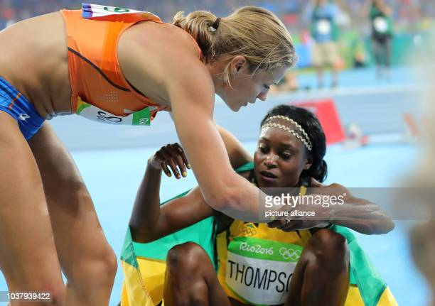 Elaine Thompson of Jamaica is hugged by silver medalist Dafne Schippers of the Netherlands after winning the Women's 200m Final of the Athletic,...