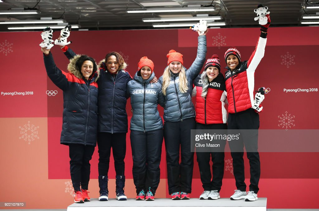Elana Meyers Taylor and Lauren Gibbs of the United States, silver, Mariama Jamanka and Lisa Buckwitz of Germany, gold, and Kaillie Humphries and Phylicia George of Canada, bronze, celebrate after the Women's Bobsleigh heats on day twelve of the PyeongChang 2018 Winter Olympic Games at the Olympic Sliding Centre on February 21, 2018 in Pyeongchang-gun, South Korea.
