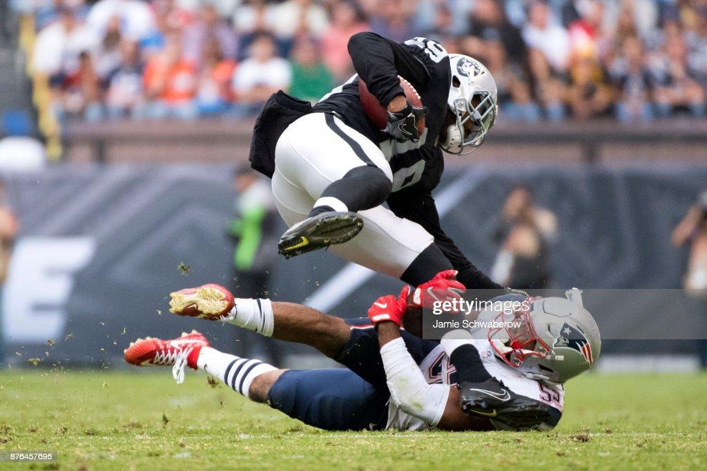 Elandon Roberts #52 of the New England Patriots tackles Jamize Olawale #49 of the Oakland Raiders at Estadio Azteca on November 19, 2017 in Mexico City, Mexico.
