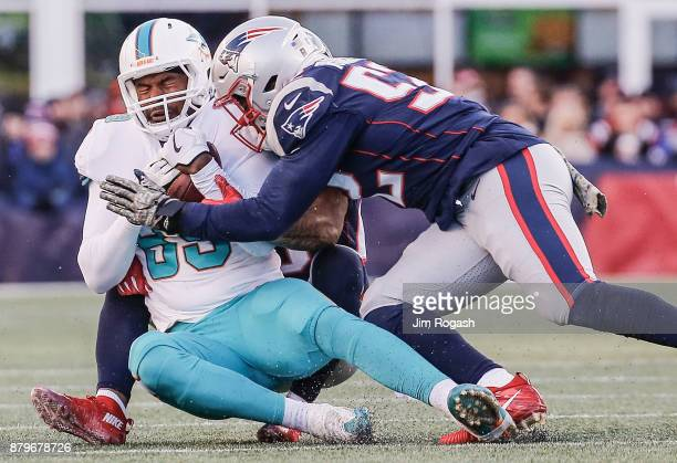 Elandon Roberts of the New England Patriots tackles Julius Thomas of the Miami Dolphins during the third quarter of a game at Gillette Stadium on...