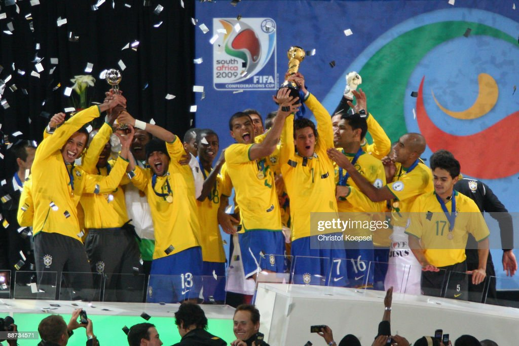 Elano of Brazil lifts the trophy as his team mates celebrate following their victory at the end of the FIFA Confederations Cup Final between USA and Brazil at the Ellis Park Stadium on June 28, 2009 in Johannesburg, South Africa.
