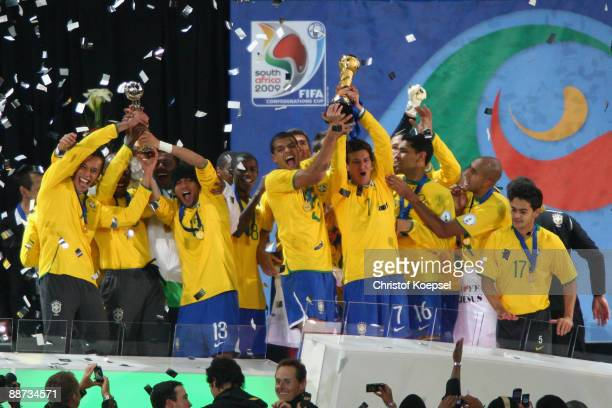 Elano of Brazil lifts the trophy as his team mates celebrate following their victory at the end of the FIFA Confederations Cup Final between USA and...