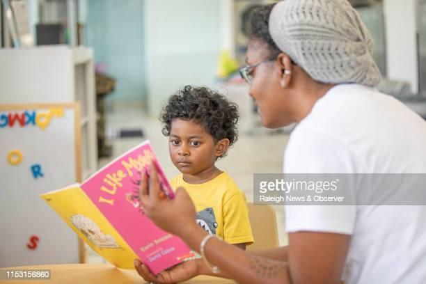 Elías Benítez de 3 años escucha a Nadiah Porter gerente de alianzas comunitarias para Book Harvest mientras le lee durante un programa llamado Lava y...
