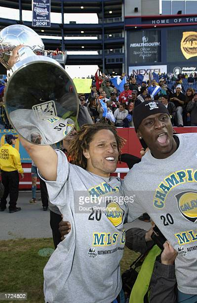 Elated captain Cobi Jones of the Los Angeles Galaxy holds the MLS Trophy in the air as he celebrates with teammate defender Ezra Hendrickson after...