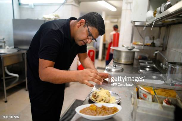 Elazar Ashtivker owner of the Maharaja Indian restaurant in the small city of Ramla south of Tel Aviv cooks at his restaurant on July 2 as the Jewish...