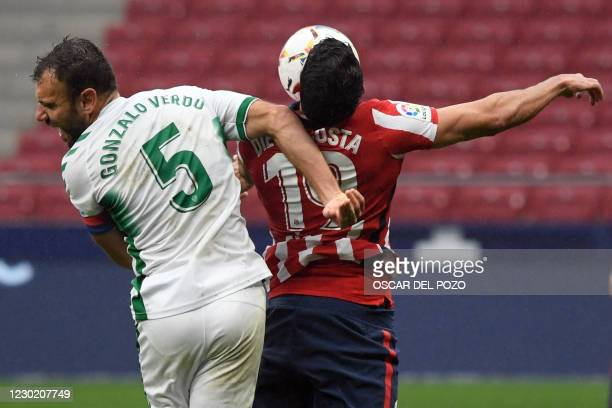Elche´s Spanish defender Gonzalo Verdu vies with Atletico Madrid's Spanish forward Diego Costa during the Spanish league football match between Club...