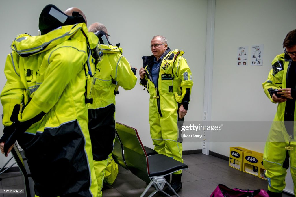 Eldar Saetre, chief executive officer of Equinor ASA, center, dresses in protective overalls before boarding a helicopter on route to the Troll A natural gas platform, operated by Equinor ASA, in the North Sea, Norway, on Wednesday, May 16, 2018. Statoil has changed its name toEquinorto reflect its mutation into a broader energy company.Photographer: Carina Johansen/Bloomberg via Getty Images