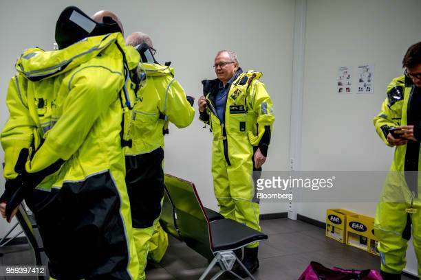 Eldar Saetre chief executive officer of Equinor ASA center dresses in protective overalls before boarding a helicopter on route to the Troll A...