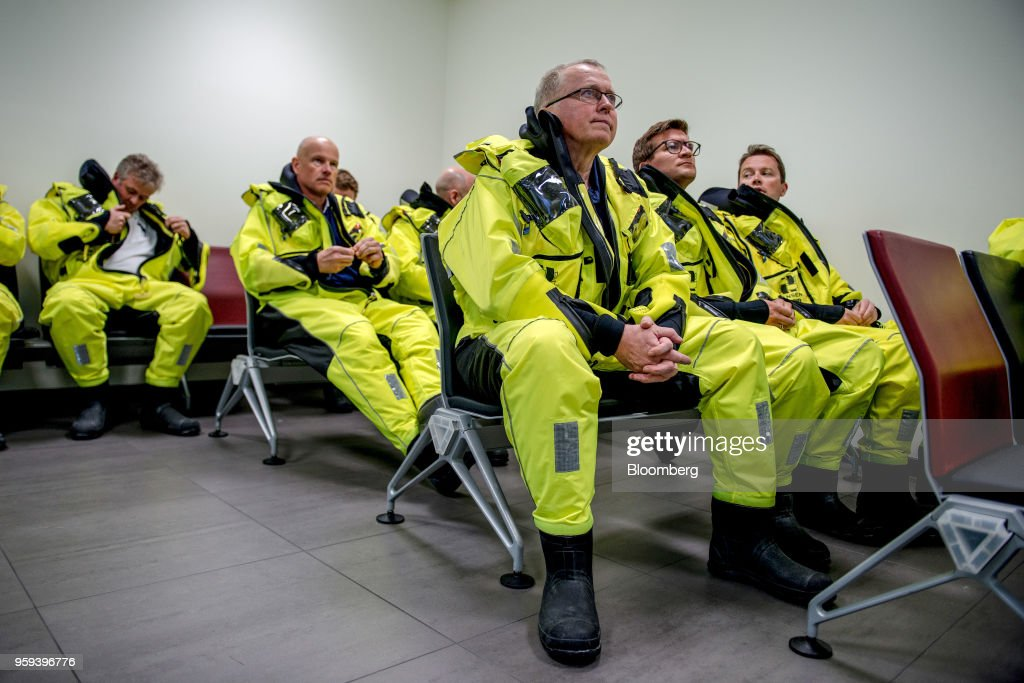 Eldar Saetre, chief executive officer of Equinor ASA, center, listens to a briefing before boarding a helicopter on route to the Troll A natural gas platform, operated by Equinor ASA, in the North Sea, Norway, on Wednesday, May 16, 2018. Statoil has changed its name toEquinorto reflect its mutation into a broader energy company.Photographer: Carina Johansen/Bloomberg via Getty Images