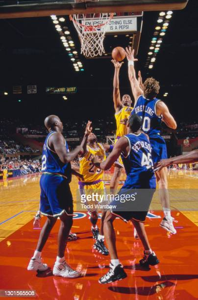 Elden Campbell, Center and Power Forward for the Los Angeles Lakers jumps to make a lay up shot to the basket as Greg Dreiling of the Dallas...