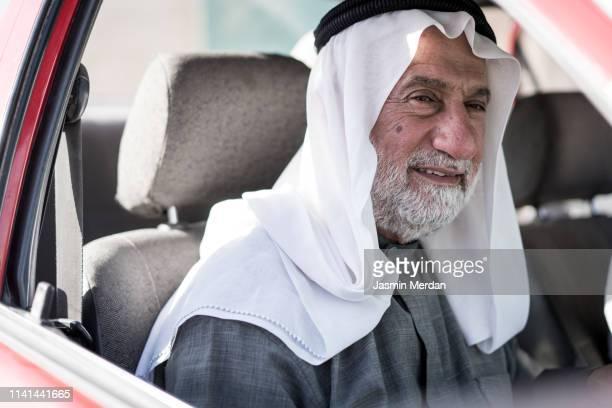 elder arab man in car - arabische kultur stock-fotos und bilder