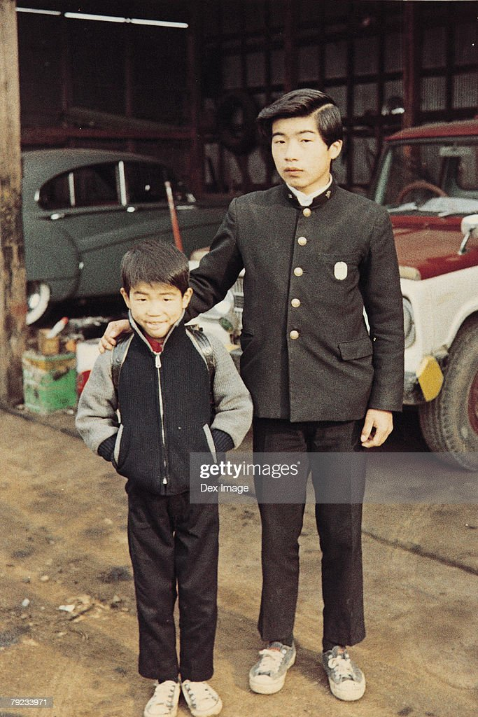 Elder brother and younger brother at garage : Stock Photo