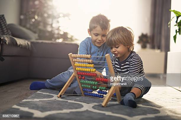 Elder brother helping little boy to count on abacus