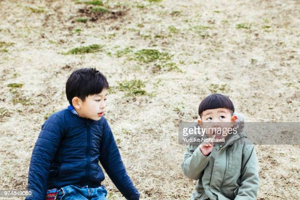 elder brother watching brother eating french fries - 噛む ストックフォトと画像