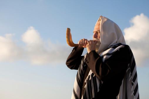 Elder Jewish man blowing a Shofar on Rosh Hashanah 168531827