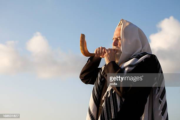 Elder Jewish man blowing a Shofar on Rosh Hashanah