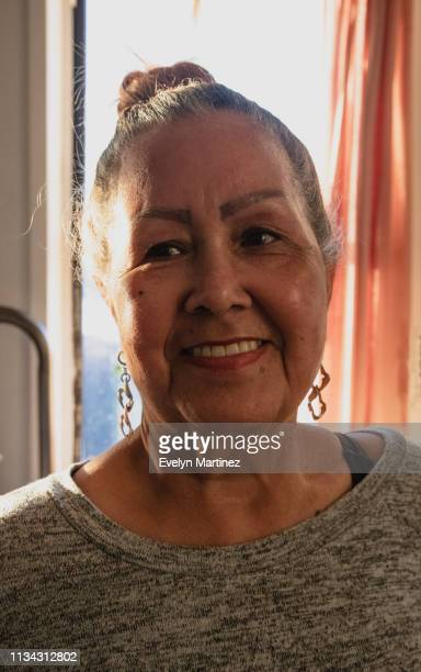 Elder Latina woman smiling, looking away. Window and plant in the background.