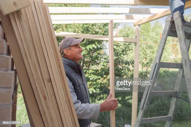 Elder man enjoying helping in the house construction process