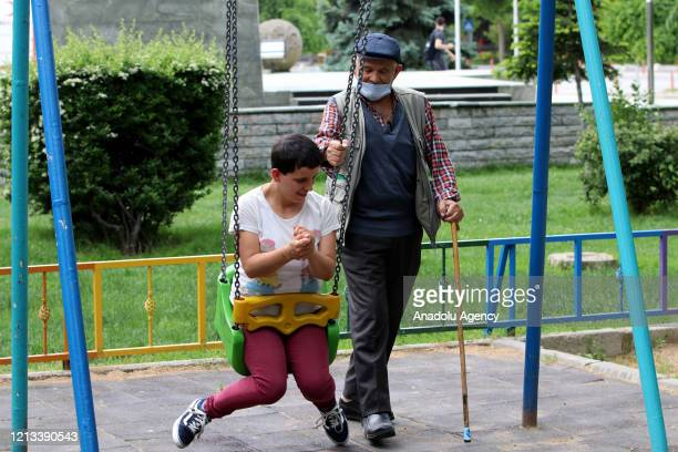 Elder man Halim Tunc is seen with his daughter Elif Tunc, with special needs, at a park after people over 65-year-old and chronic diseases are...