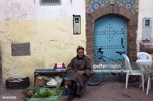 Elder man in djellaba selling cigarettes and vegetables at his street stall in the Medina