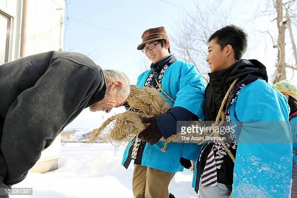 A elder man makes his head bitten by a 7meterlong 30kilogram straw snake carried by school pupils in hope of good health during the HebinoGonenshi or...