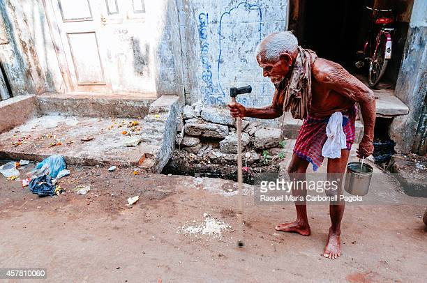 Elder man wearing only a lungi tries to walk the streets helped by a crutch