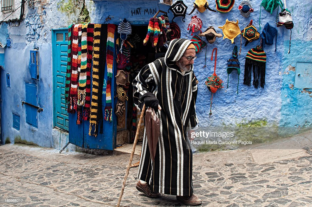 CONTENT] Elder man wearing traditional djellaba passing by a souvenirs shop in the blue medina. Chefchaouen, Rif region, Morocco. 2012