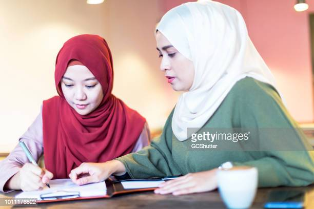 elder sister assisting her sister filling a job application form - free business coaching stock pictures, royalty-free photos & images