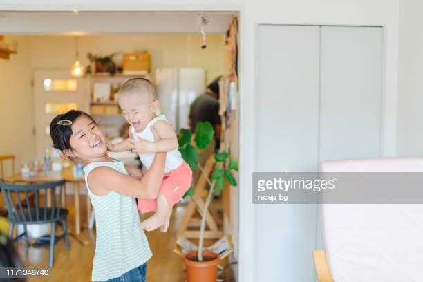 彼女の赤ちゃんの弟と遊ぶ姉 - 兄弟 ストックフォトと画像