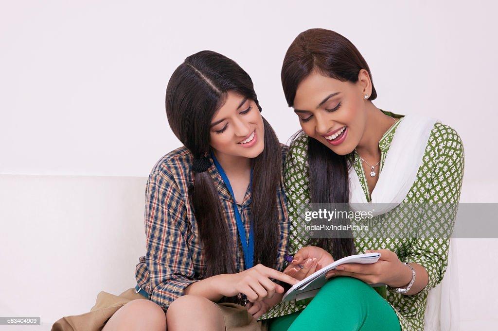 Elder sister teaching younger sister : Stock Photo