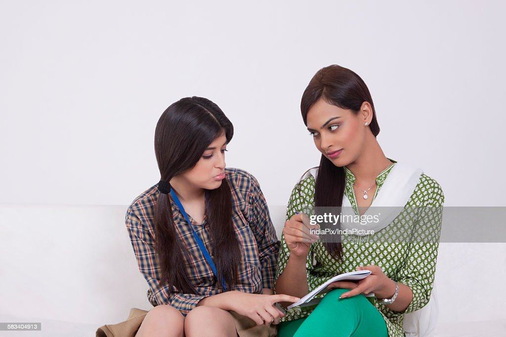 Elder sister teaching younger sister : Stock Photo