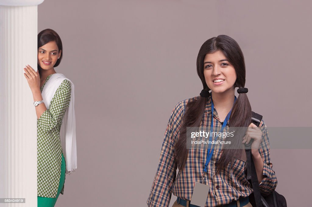 Elder sister watching younger sister leave for school : Stock Photo