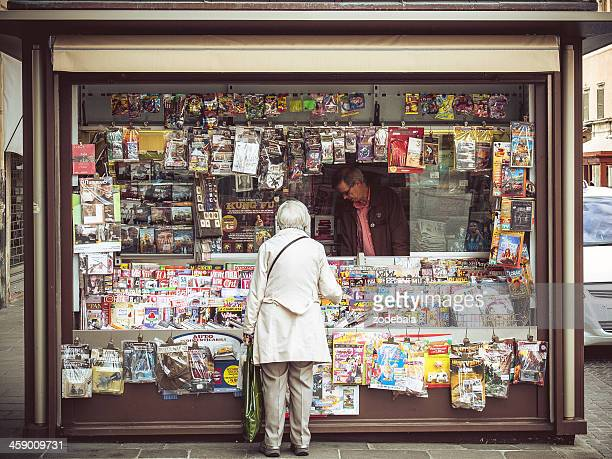 elder woman buying magazine at italian news stand - news stand stock pictures, royalty-free photos & images