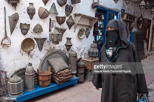 Elder woman in traditional niqab passing by a lamps shop in Essaouira medina, World Heritage site, Morocco. 2013