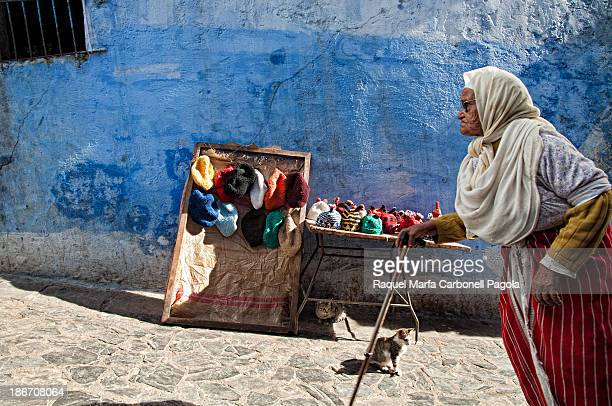 CONTENT] Elder woman traditionally dressed passing by a souvenirs shop in the blue medina of Chefchaouen Morocco 2012