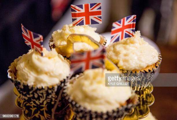 Elderflower cupcakes decorated with the Union Jack are served while a group of women watch the Wedding of Prince Harry and Meghan Markle from the...