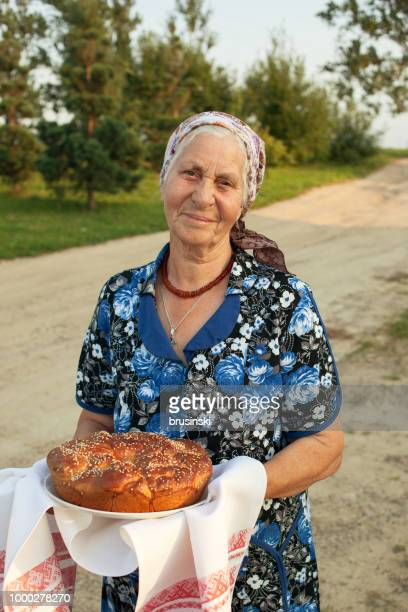 elderly 80 year old woman meets guests with traditional food - belarus stock pictures, royalty-free photos & images
